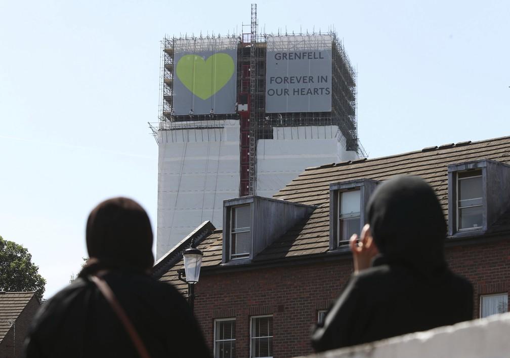 -  Mulheres observam faixa pendurada na Torre Grenfell, em Londres:   39;Para sempre em nossos corações  39;  Foto: Yui Mok/PA via AP