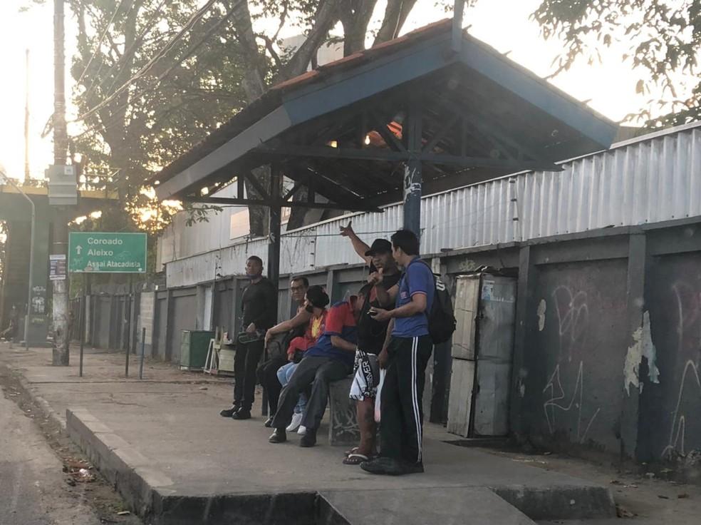 Trabalhadores aguardam em ponto de ônibus de Manaus, que amanheceu sem transporte após ataques — Foto: Matheus Castro/G1