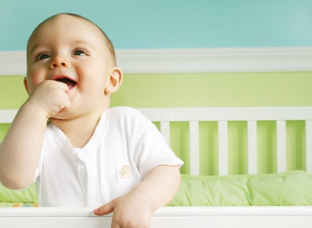 Bebe rindo no berço (Foto: Shutterstock)