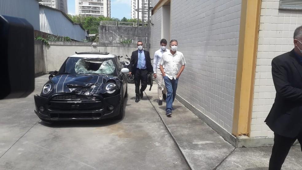 Marcinho, ex-Botafogo, e o pai Sergio Lemos de Oliveira saem da delegacia ao lado do carro do acidente — Foto: Davi Barros / ge
