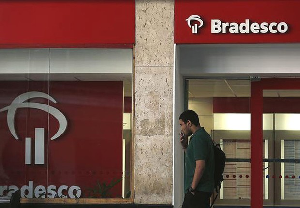 Homem passa diante da agência do Bradesco (Foto: Pilar Olivares/Reuters)