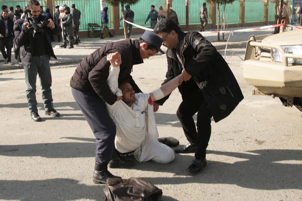Ferido recebe ajuda após explosão de carro-bomba em Cabul, no Afeganistão, neste sábado (27)  (Foto: Massoud Hossaini/ AP)
