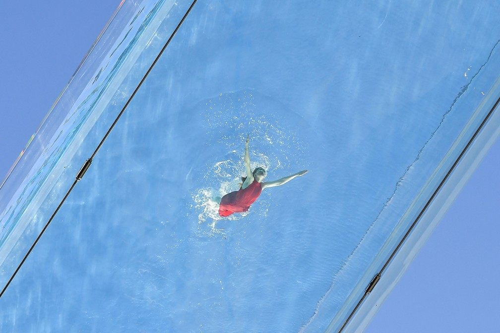 Uma modelo nada em uma piscina de acrílico transparente fixada entre dois blocos de apartamentos em Embassy Gardens, em Londres — Foto: Justin Tallis/AFP