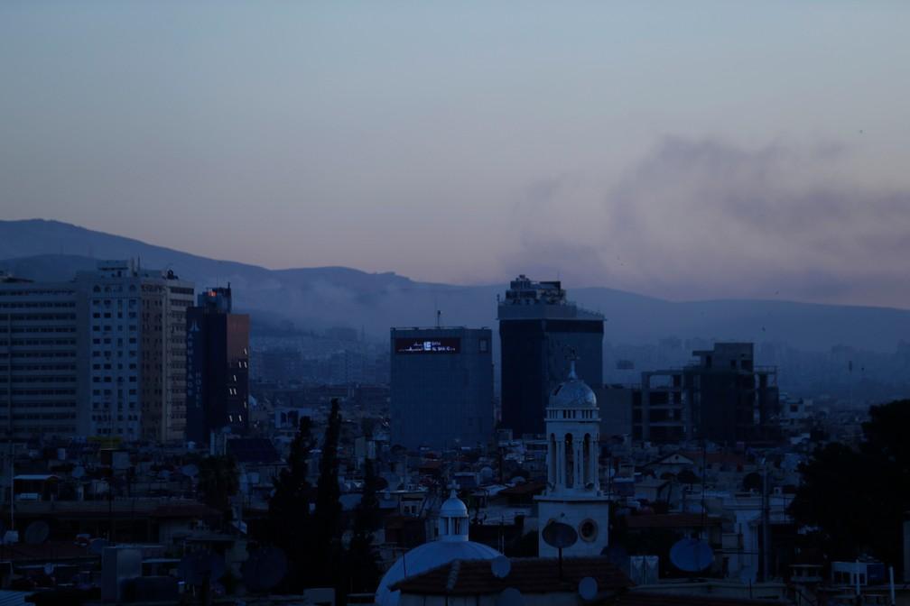 Vista de Damasco, capital da Síria, com uma coluna de fumaça no céu (Foto: Hassan Ammar/AP Foto)