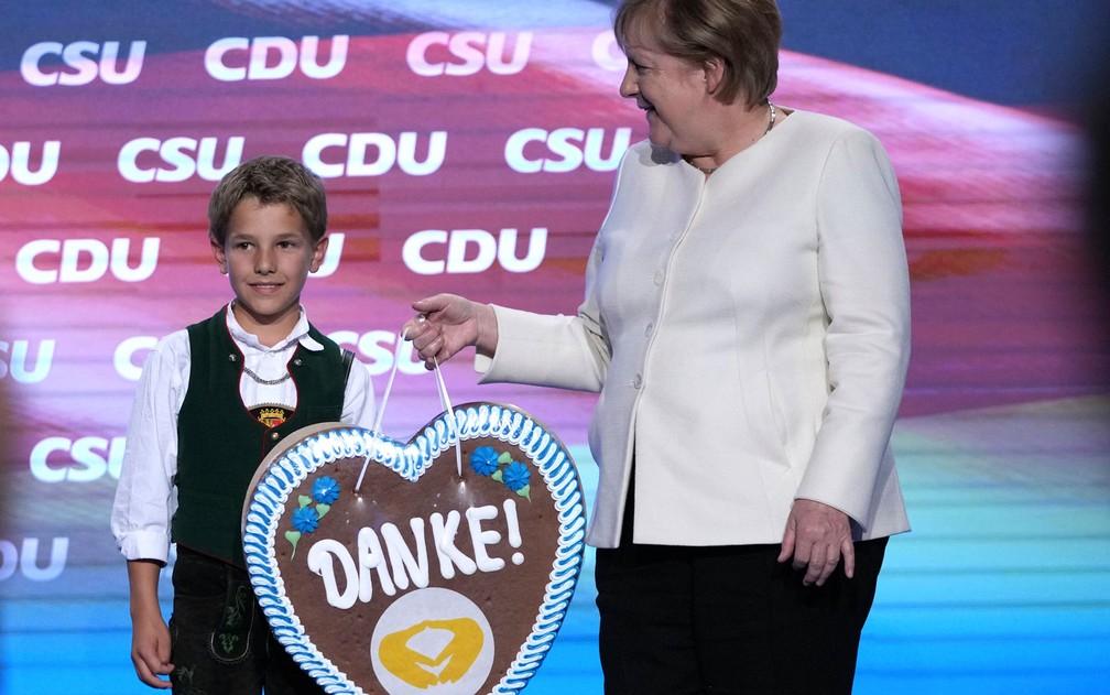 """Menino com traje típico da região da Baviera entrega à primeira-ministra alemã Angela Merkel um biscoito gigante com a palavra """"obrigado"""", durante evento de campanha da CDU em Munique, na sexta-feira (24) — Foto: AP Photo/Matthias Schrader"""