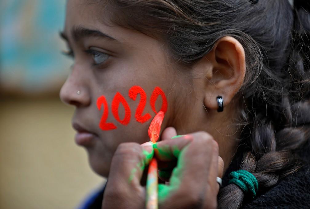 Menina faz pintura de '2020' no rosto em Ahmedabad, na Índia, para celebrar o Ano Novo nesta terça (31). — Foto: Amit Dave/Reuters
