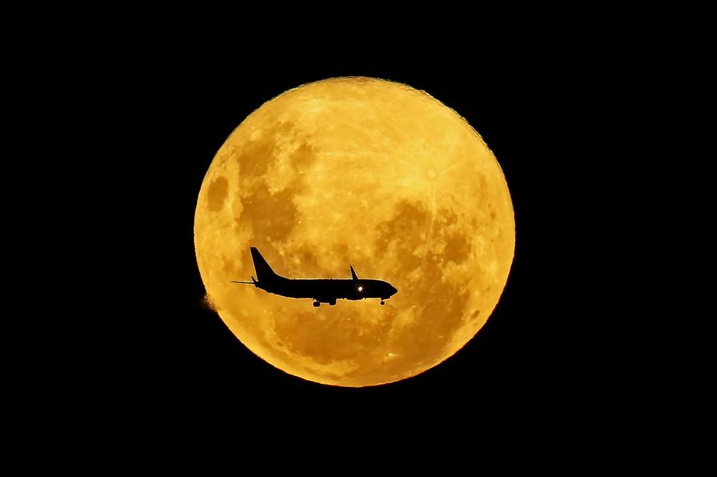 9 de março - Um avião passa em frente à lua cheia vista de Curitiba. A superlua é visível quando a lua cheia coincide com sua posição mais próxima da Terra, o que a faz parecer mais brilhante e maior que outras luas cheias — Foto: Heuler Andrey/AFP