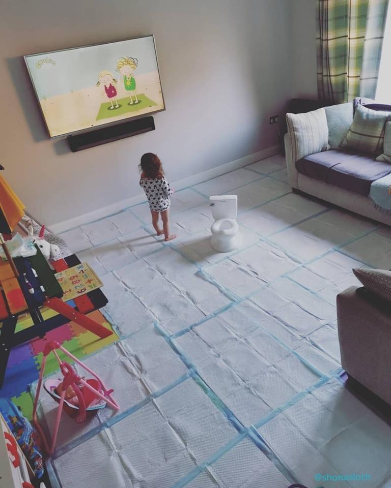 Criança assiste TV tranquilamente enquanto mãe a ensina a usar o penico. O chão do comodo foi completamente forrado para evitar vazamentos (Foto: Shona McLoughlin/Reprodução)