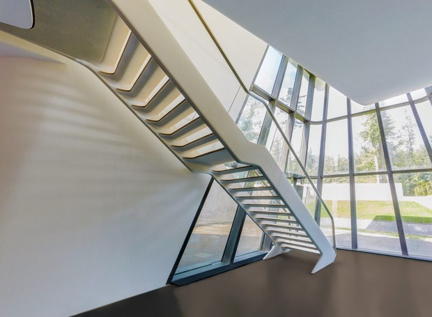 O interior também é futurista com uma escada irregular e as paredes de vidro (Foto: OKO Group)