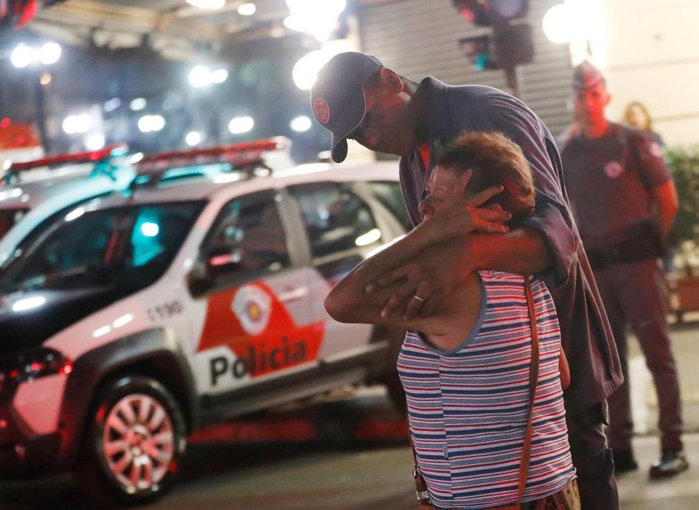Bombeiro consola mulher durante incêndio no Centro de São Paulo (Foto: Leonardo Benassatto/Reuters)