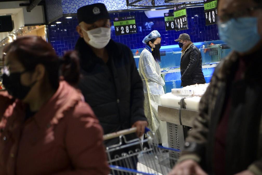 Mulher veste máscara, capa e cobre a cabeça com um saco plástico enquanto se abastece em um mercado de Wuhan, considerado epicentro da epidemia de coronavírus na China — Foto: Chinatopix/AP