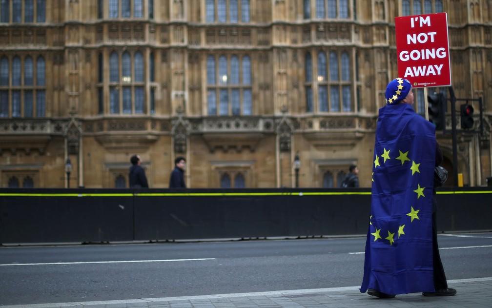 Manifestante anti-Brexit segura placa com a inscrição 'não vou embora' em frente ao Parlamento, em Londres, no dia 20 de março — Foto: Reuters/Hannah McKay