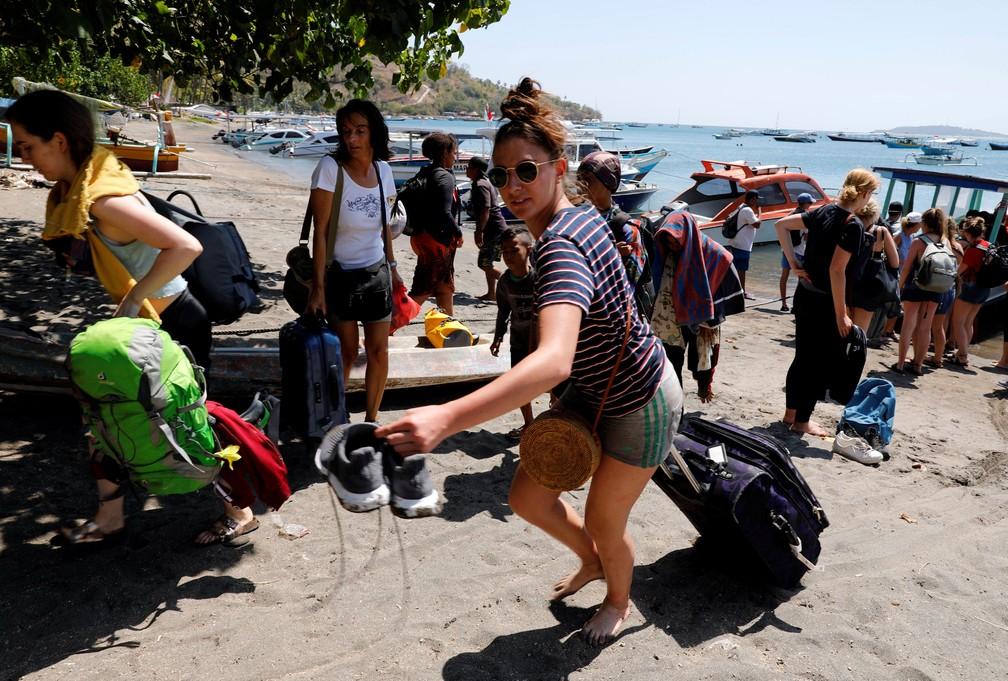 Turistas estrangeiros deixam ilha de Gili nesta segunda-feira (6). Terremoto atingiu a região no domingo (5)  (Foto: Beawiharta/ Reuters)
