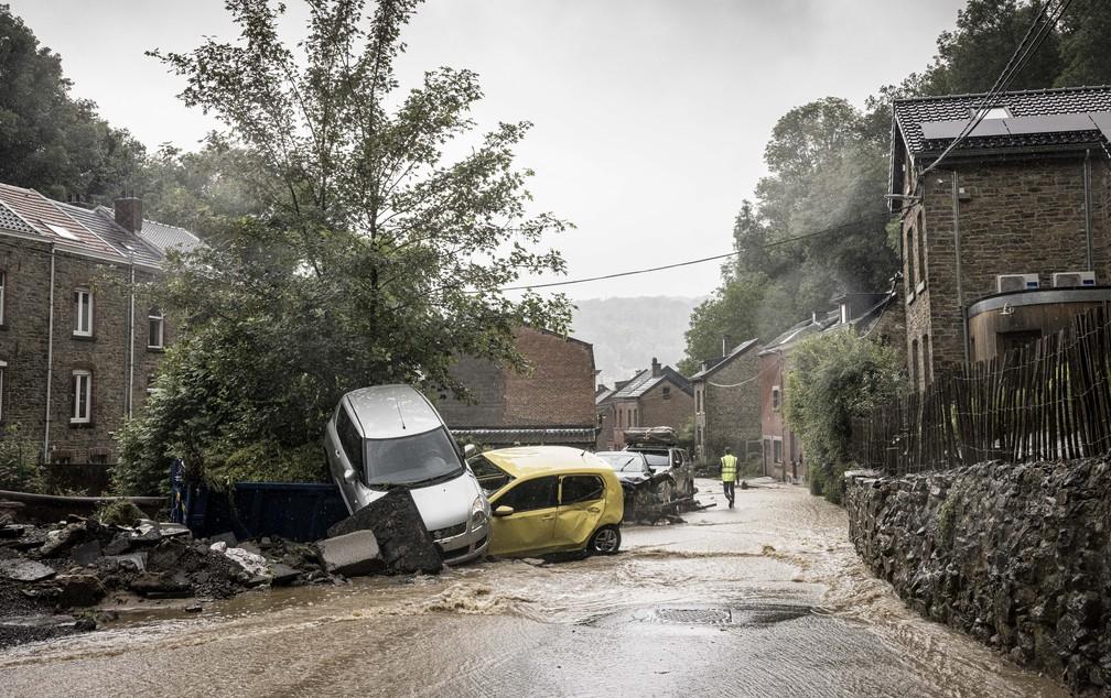 Homem caminha perto de carros danificados pela água em rua inundada em Mery, na província de Liege, na Bélgica, em 14 de julho de 2021 — Foto: Valentin Bianchi/AP