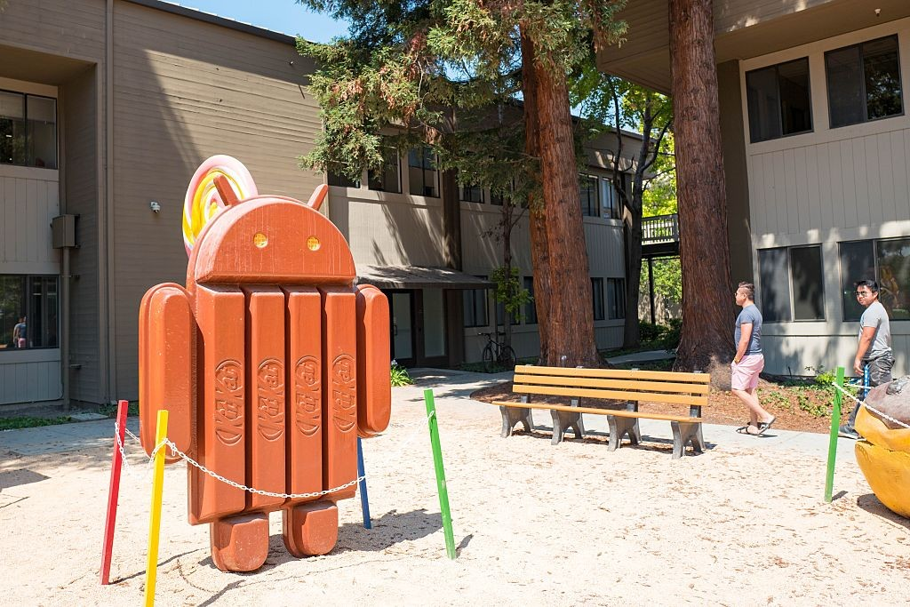 "Two men walk near a sculpture representing Version 4.4 of the Android cellphone operating system, which was nicknamed ""Kit Kat"", at the Googleplex, headquarters of the search engine company Google in the Silicon Valley town of Mountain View, California, A (Foto: Getty Images)"