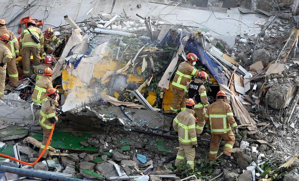 Bombeiros sul-coreanos procuram por passageiros em ônibus soterrado pelos destroços de prédio que desabou em Gwangju, na Coreia do Sul, em 9 de junho de 2021 — Foto: Yonhap via Reuters