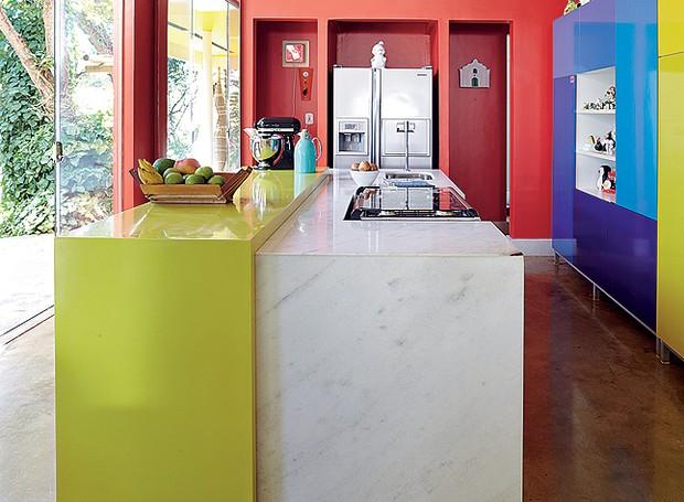Em mármore branco, a ilha central harmoniza a cozinha de cores fortes. Parte da bancada é de laca verde. Quem assina a criação é o arquiteto Leo Romano (Foto: Victor Affaro/Editora Globo)