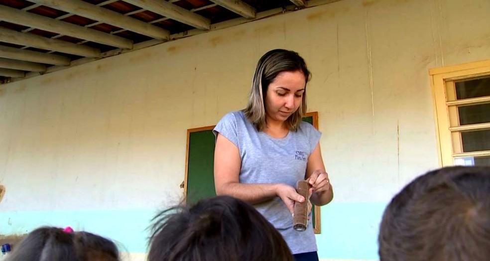 A auxiliar de serviços gerais Viviane Lopes durante distribuição de lanche aos alunos: