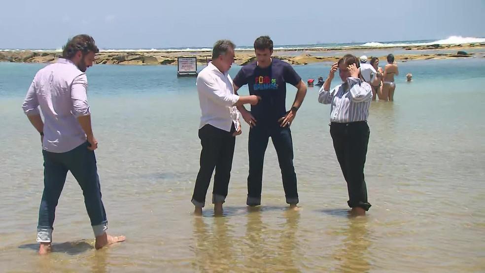 Ministro do Turismo [de azul escuro] molha os pés em Muro Alto, em Ipojuca, uma das localidades atingidas por óleo no Nordeste — Foto: Reprodução/TV Globo