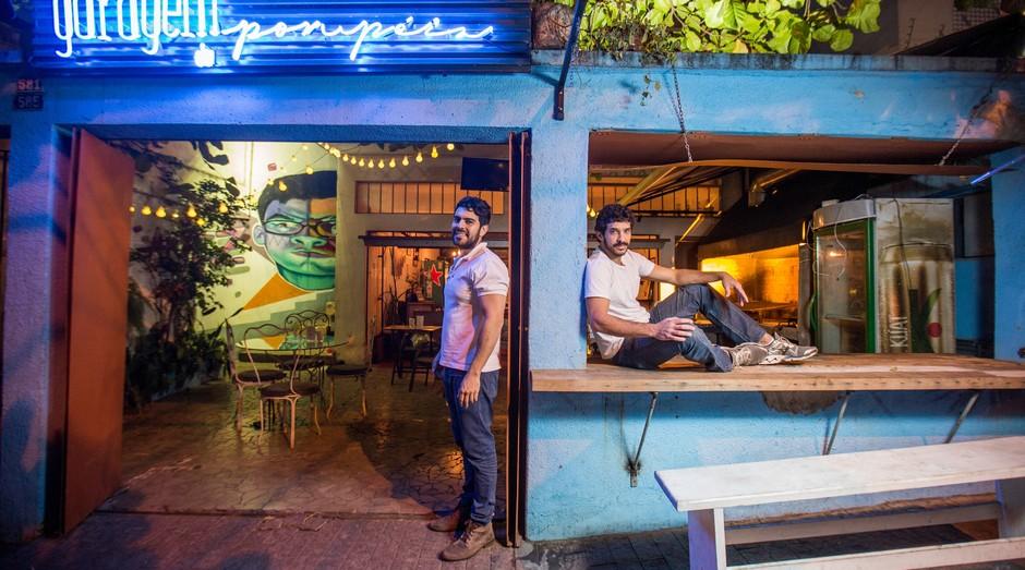 Igor Macedo (direita) e Cristiano Nunes são proprietários do Garagem Pompeia Bar, estabelecimento que prosperou na garagem da residência deles onde mantinham um hostel, e hoje o bar tornou-se a principal atividade do empreendimento.  (Foto: Reprodução/Agência Sebrae-SP)