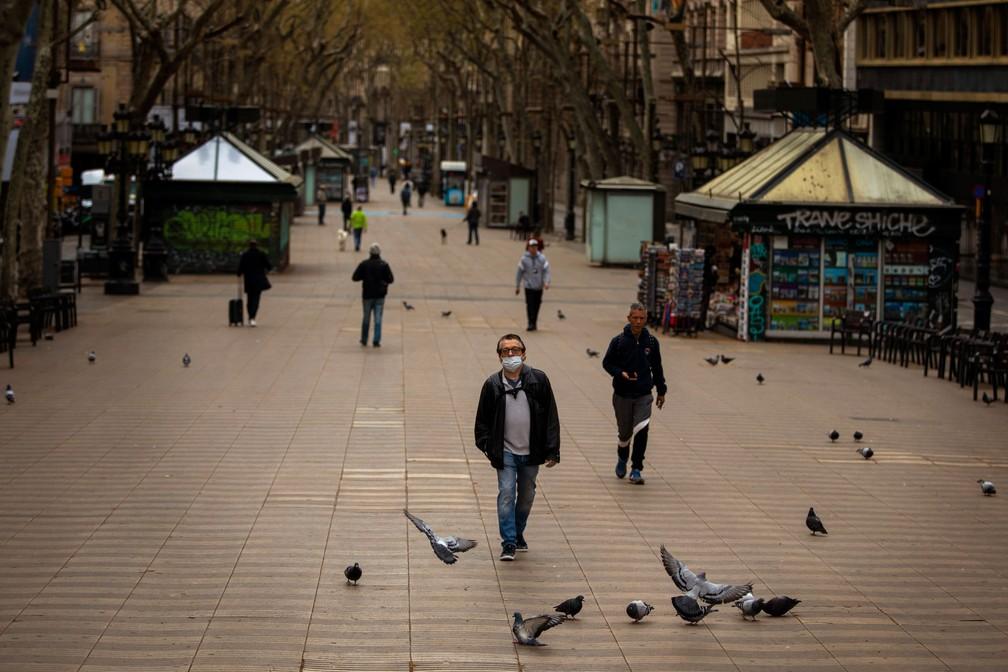 Pessoas caminham em Las Ramblas, via que é um tradicional ponto turístico em Barcelona, na Espanha, neste domingo (15)  — Foto: Emilio Morenatti/AP