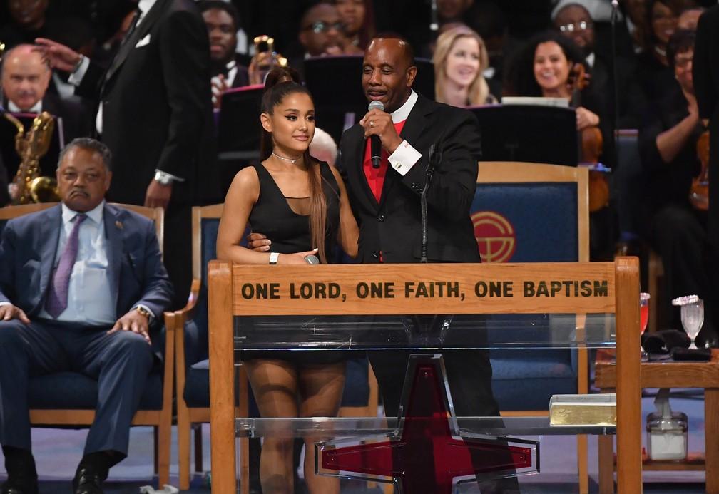 Ariana Grande é segurada pelo bispo Charles H. Ellis III (Foto: Angela Weiss / AFP)