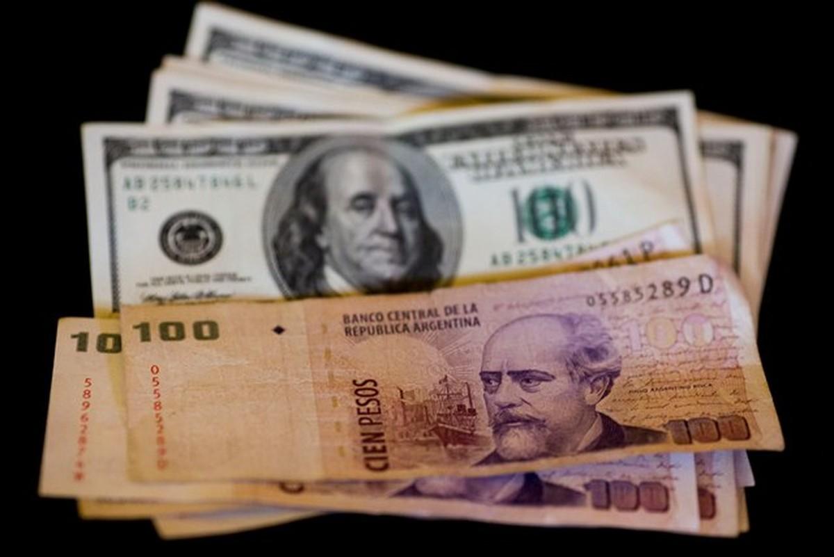 A imagem contém algumas notas de dólar e de peso argentino.