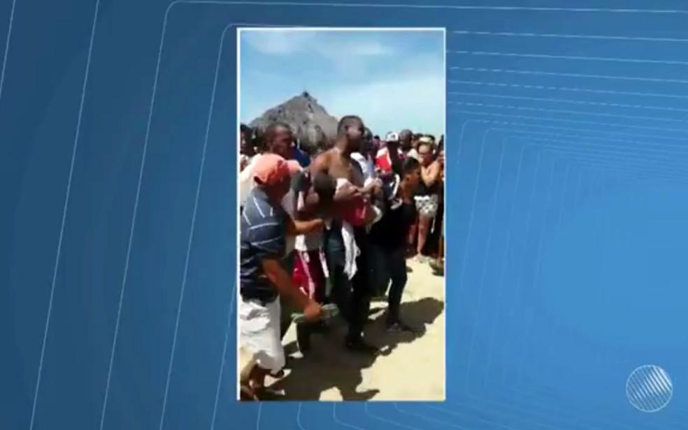Pai carrega corpo do filho, após acidente com embarcação (Foto: Reprodução/TV Bahia)