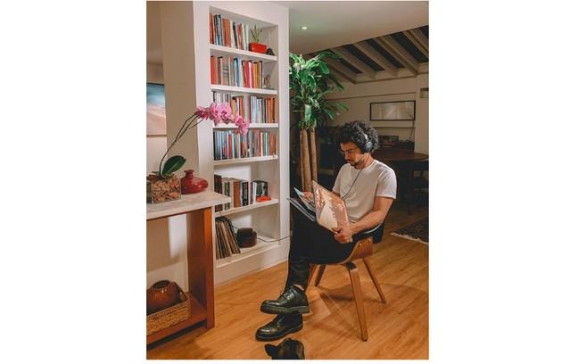O ator na estante com livros e discos: 'Como é a segunda casa onde moramos, trouxemos móvel e peças que já tínhamos. Não gosto de tudo novo. Casa precisa ter história' (Foto: Reprodução)