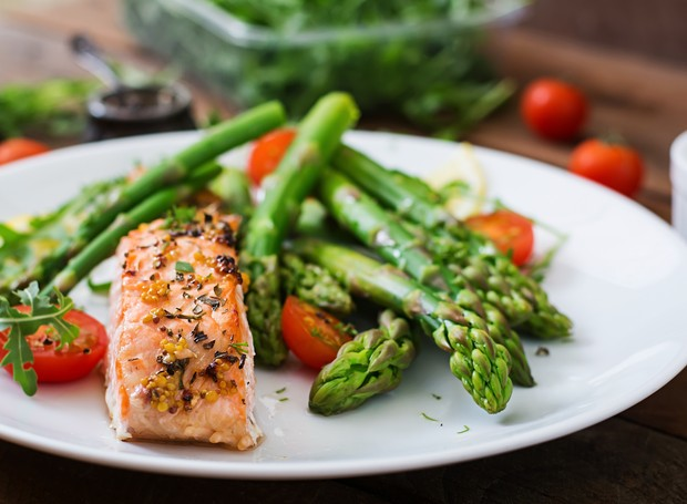 Baked salmon garnished with asparagus and tomatoes with herbs (Foto: Getty Images/iStockphoto)