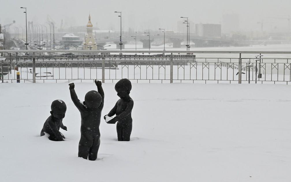 Esculturas de crianças brincando são vistas cobertas de neve em Kiev, na Ucrânia, na sexta-feira (12) — Foto: Sergei Supinsky/AFP