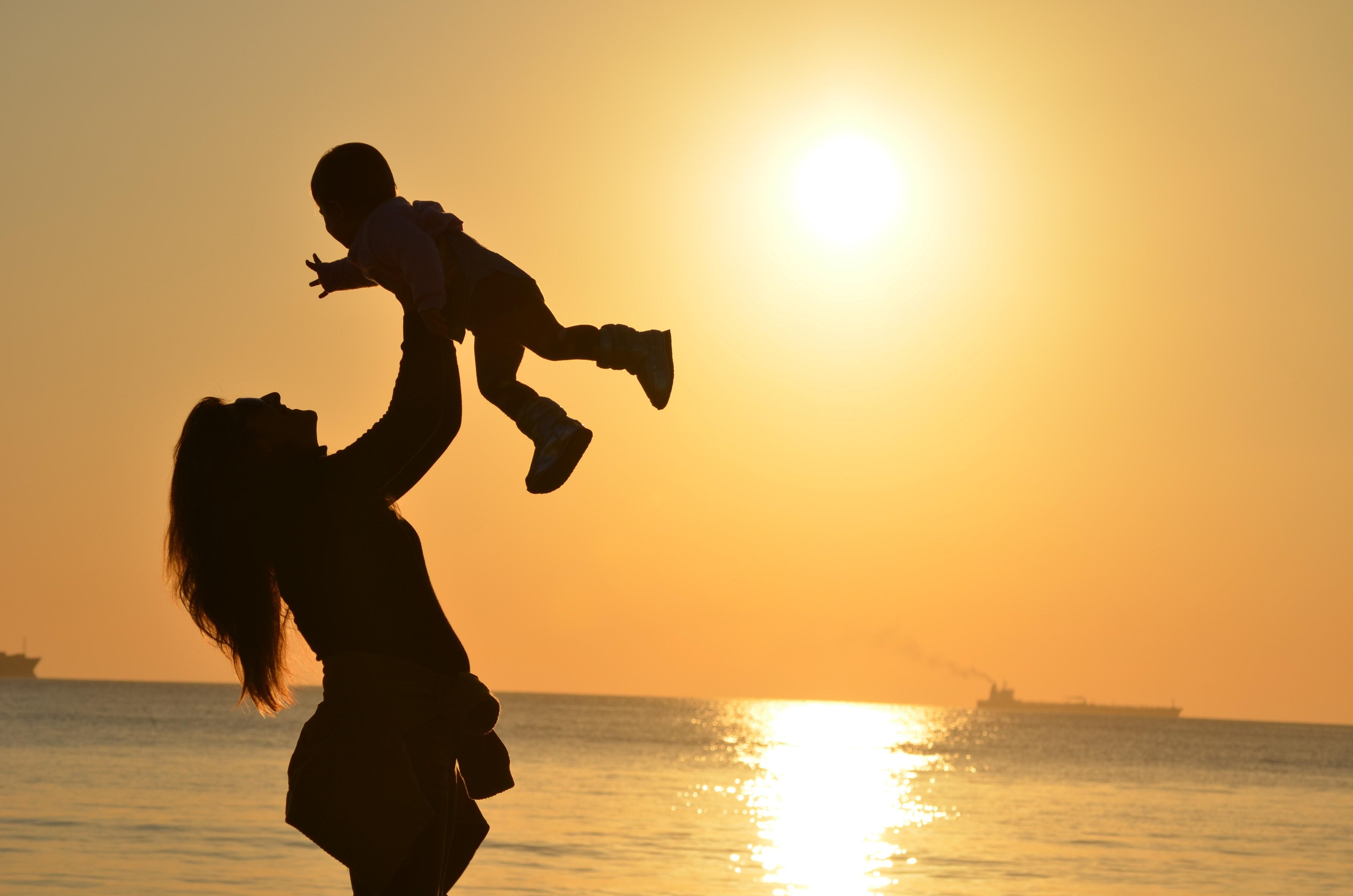 Mãe brinca com filho na praia ao entardecer (Foto: Pixabay/Pexels)