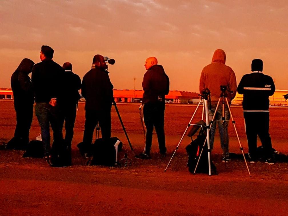 Grupo de fotógrafos no amanhecer em Viracopos, aeroporto de Campinas. — Foto: Luciano Calafiori/G1