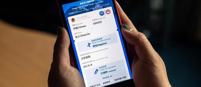 """Mulher segura um celular exibindo simulação do novo certificado de saúde digital da China, o """"passaporte da vacina"""", em Pequim"""