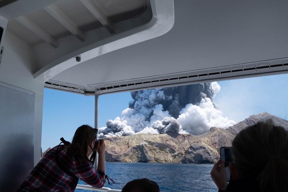 Turistas fotografam o vulcão da Ilha Branca, na Nova Zelândia, logo após o início da erupção  — Foto: Michael Schade
