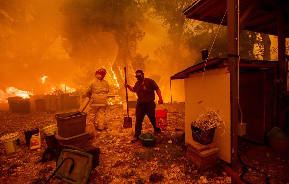 Moradores tentam salvar casa em New Long Valley, na Califórnia, no sábado (4) (Foto: Noah Berger / AFP)