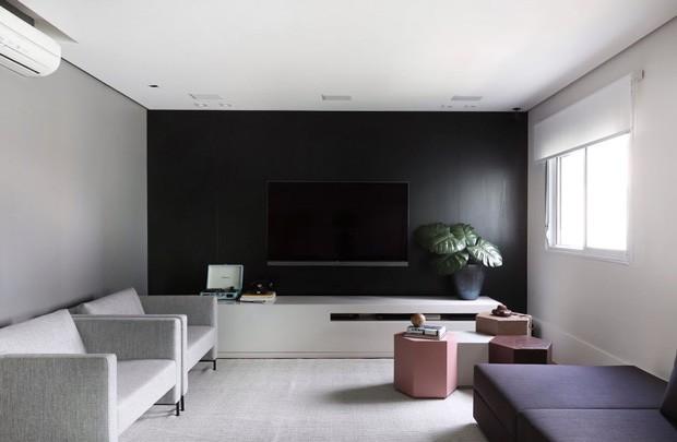 SALA DE ESTAR | O sofá, o rack abaixo da televisão e as poltronas são da Micasa. O tapete é da By Kamy. As mesinhas coloridas são da KMM Design (Foto: Mariana Orsi / Divulgação)