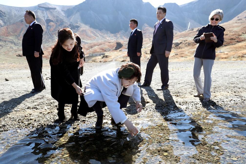 A primeira dama sul-coreana, Kim Jung-sook, enche uma garrafa de plástico com água do lago do Paraíso do Monte Paektu, na Coreia do Norte — Foto: Pyeongyang Press Corps/Pool via  Reuters