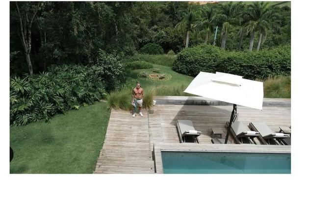 Marcos Mion posa na área externa de sua casa em São Paulo. Ao fundo, a lareira no jardim (Foto: Reprodução)