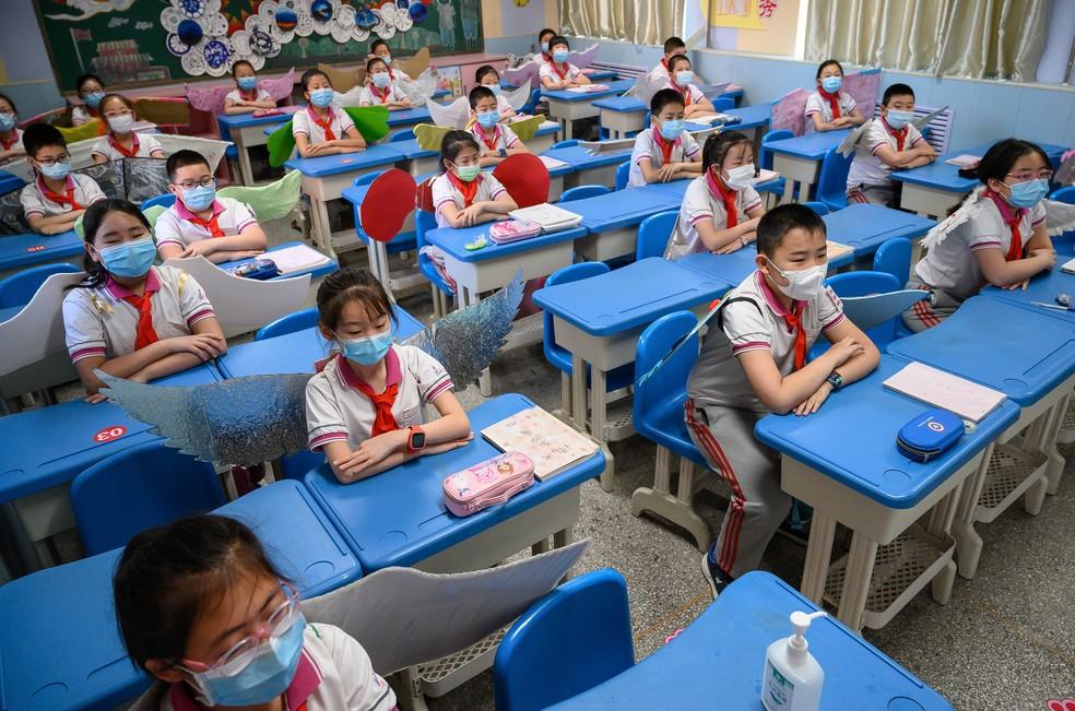 Alunos do ensino fundamental usam asas para manter o distanciamento na sala de aula em Taiyuan, na província de Shanxi, no norte da China. Foto tirada em 20 de maio de 2020 — Foto: AFP