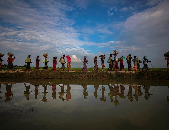 Rohingyas atravessam uma área de plantação de arroz após fugir de Mianmar (Foto: FOTÓGRAFOS/REUTERS)