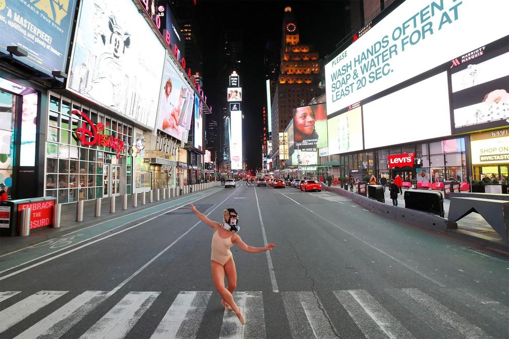18 de março - A bailarina e performer Ashlee Montague usa uma máscara de gás enquanto dança na Times Square, famosa praça de Nova York, que está com movimento bem menor que o normal devido às restrições do coronavírus — Foto: Andrew Kelly/Reuters