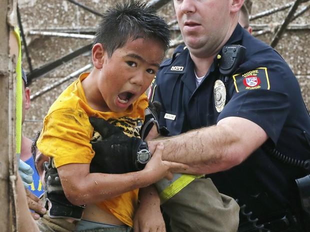Menino é retirado de escombros de uma parede que ruiu na escola primária Plaza Towers em Oklahoma City após a passagem do tornado. (Foto: Sue Ogrocki/AP)