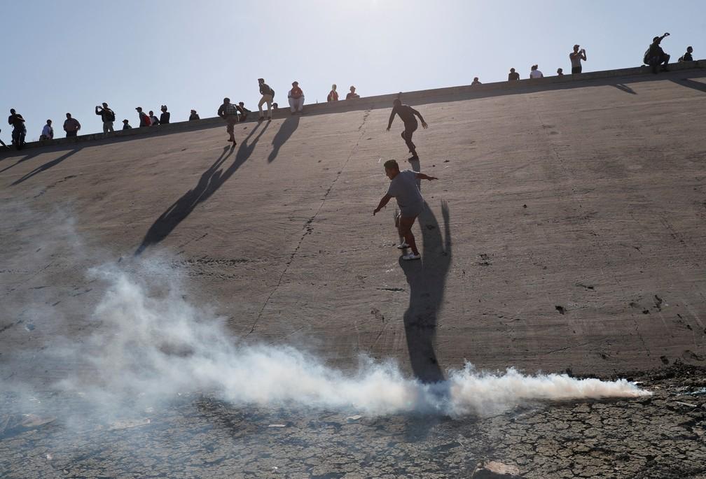 Oficiais dos EUA usam gás lacrimogêneo para conter imigrantes — Foto: Reuters