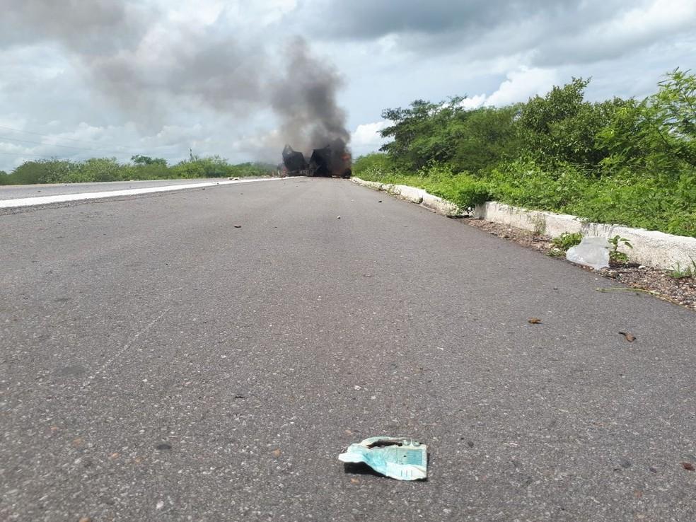 Parte de uma nota de Real à beira da BR-304; ao fundo, o carro-forte explodido por assaltantes no RN  (Foto: Sara Cardoso/Inter TV Costa Branca)