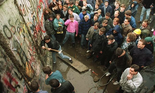 Com uma picareta, um homem derruba parte do Muro de Berlim, observado por uma multidão