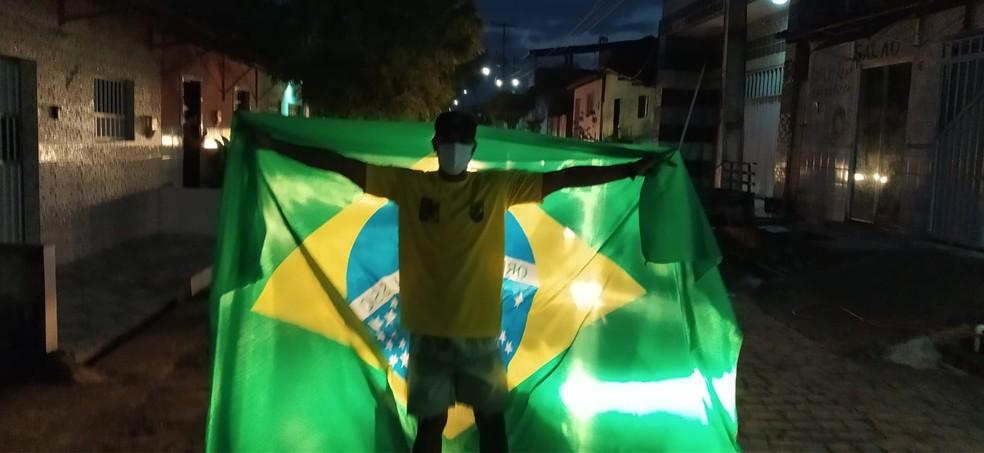 Eberton Tanoeiro exibe bandeira do Brasil ao comemorar ouro de Italo Ferreira em Baía Formosa (RN) nesta quinta (27) — Foto: Fernanda Zauli/G1