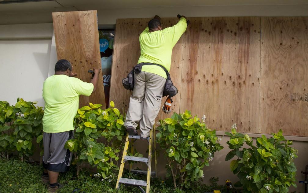 Funcionários colocam placas de madeira em janelas de vidro de uma lanchonete antes da chegada do furacão Lane, na Kalaukaua Ave, em Honolulu, no Havaí, na quarta-feira (22) (Foto: Kat Wade/Getty Images/AFP)