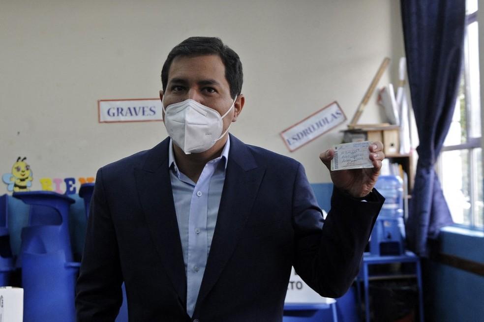 O candidato presidencial de esquerda equatoriano Andres Arauz mostra um certificado dado a ele na Junta Eleitoral de Quito durante o segundo turno das eleições de 11 de abril de 2021. Os equatorianos elegem seu próximo presidente no domingo com os eleitores escolhendo entre um jovem socialista protegido do ex-líder Rafael Correa e um conservador veterano, já que o país rico em petróleo enfrenta uma crise econômica agravada pela pandemia da Covid-19. — Foto: Camila BUENDIA / AFP
