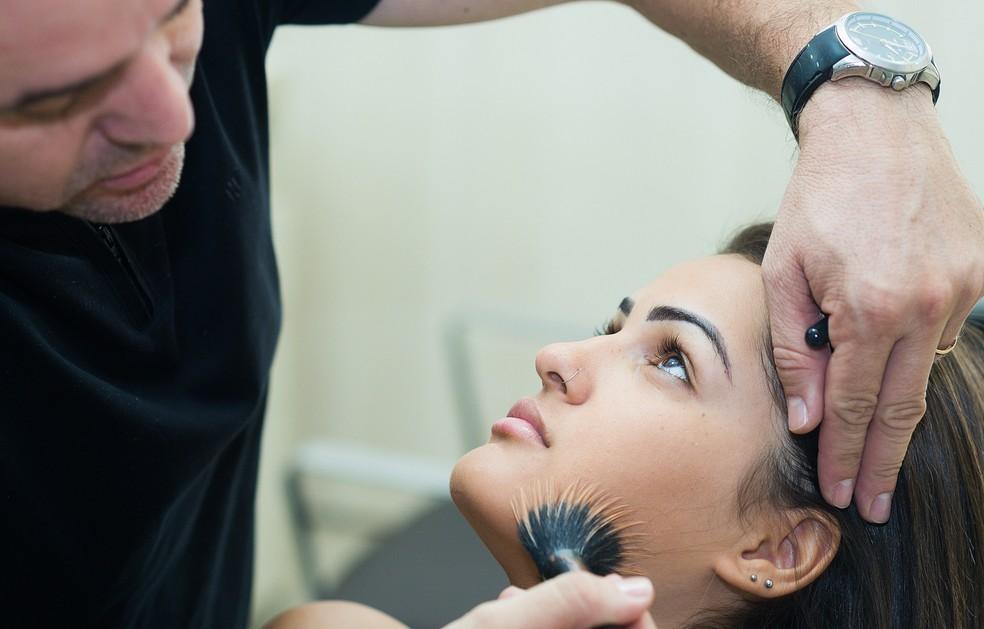 Jorge usa pincel para espalhar a base na pele de Isabela (Foto: Érico Andrade/G1)
